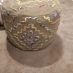 Pouff rivestito in canapa e fili di lana.