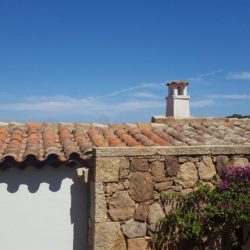 Parete in granito sardo a spacco - coppi in cotto antico - Sardegna.