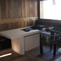 Boiserie in larice antico - tavolo in rovere sbiancato -  sedia in ferro grezzo.